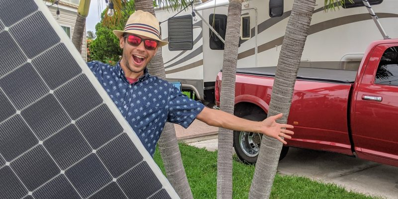 tom holding solar panel