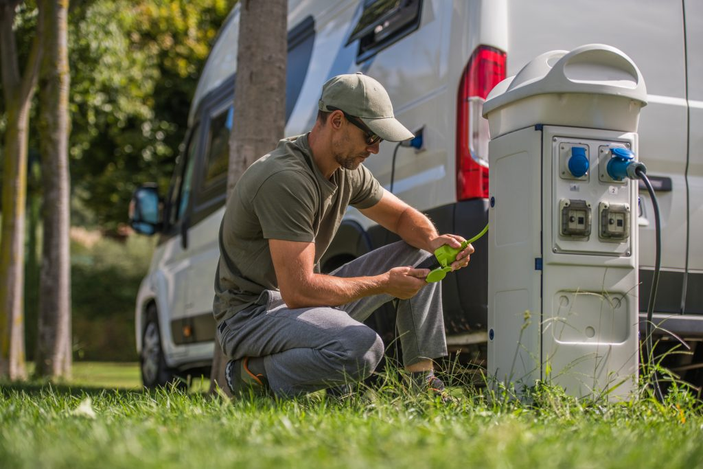 man plugging in rv to electric pedestal
