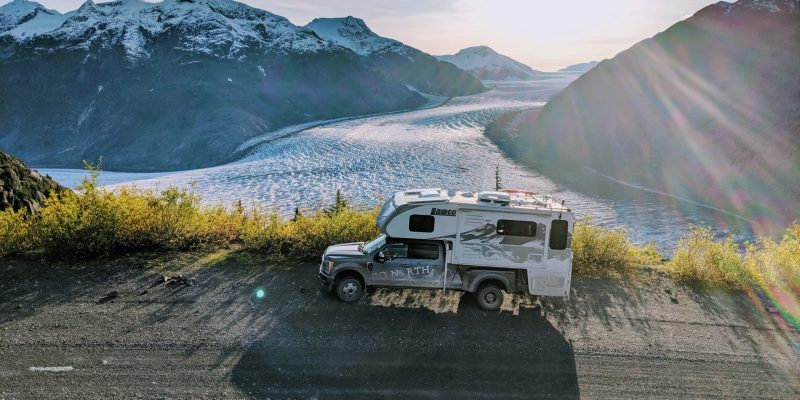 off road truck camper in front of glacier