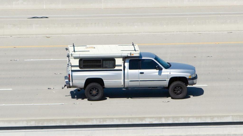 aerodynamic pop up truck camper driving on road