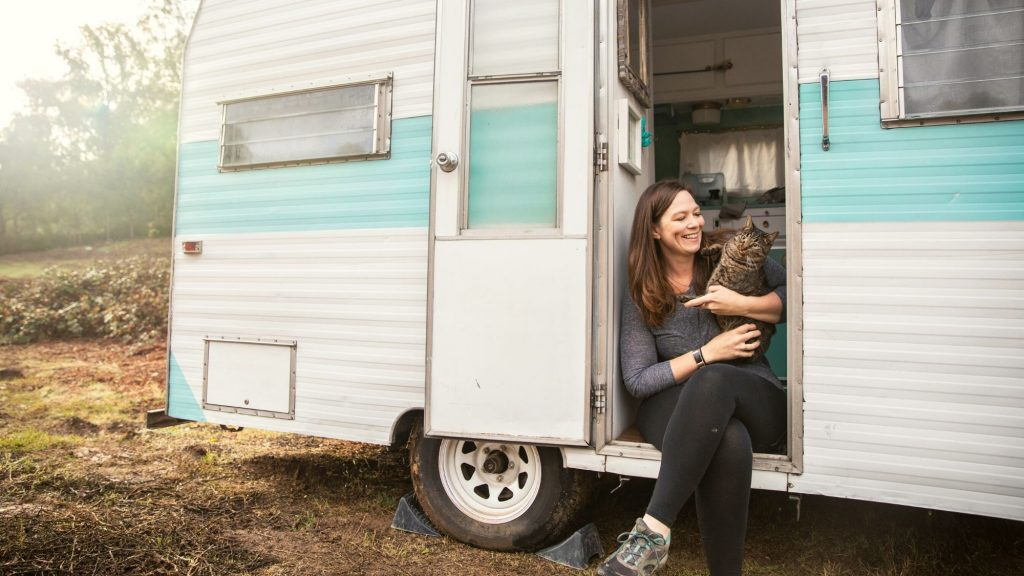 woman with cat in camper door