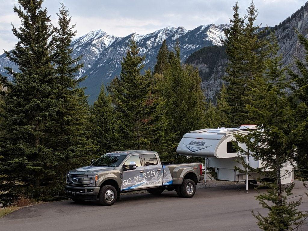 unloaded truck camper on corner-mounted jacks