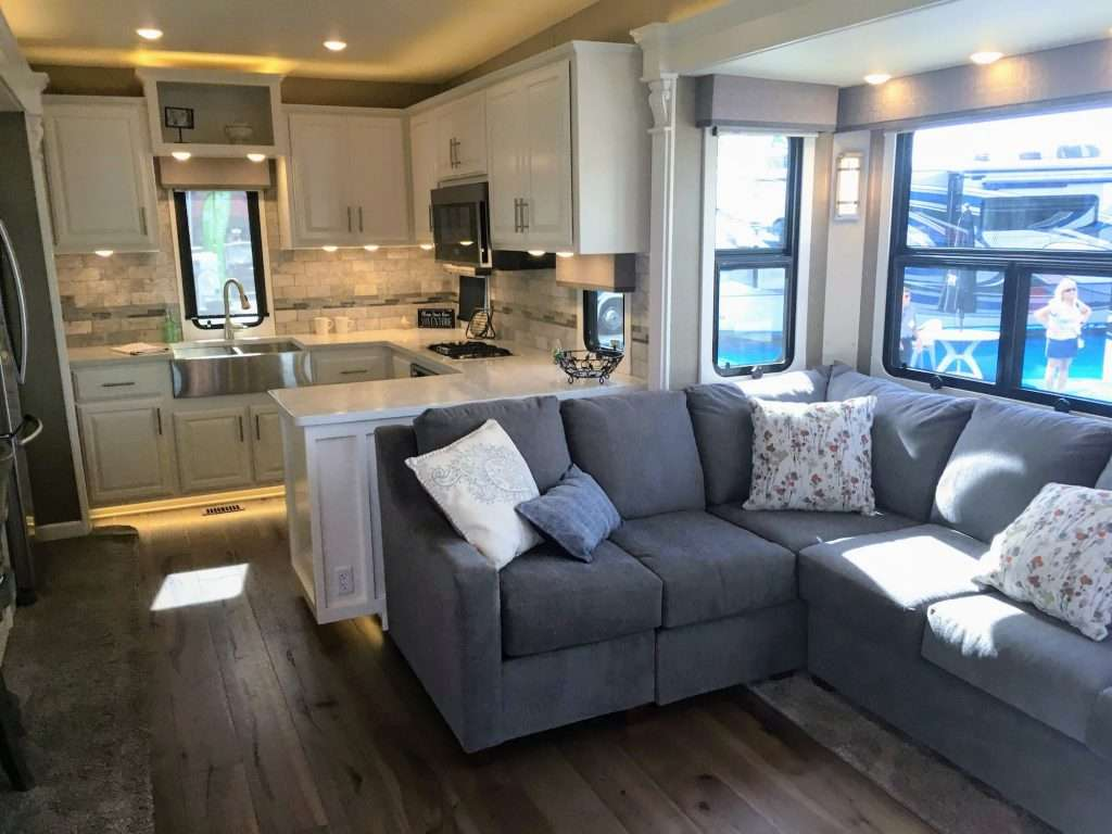 Full residential wrap-around couch in new horizons rv with rear kitchen fifth wheel