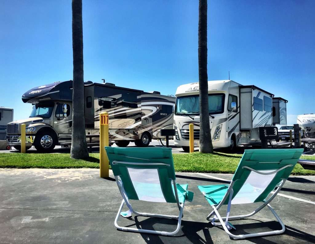 2 lawn chairs set up in front of an RV park.