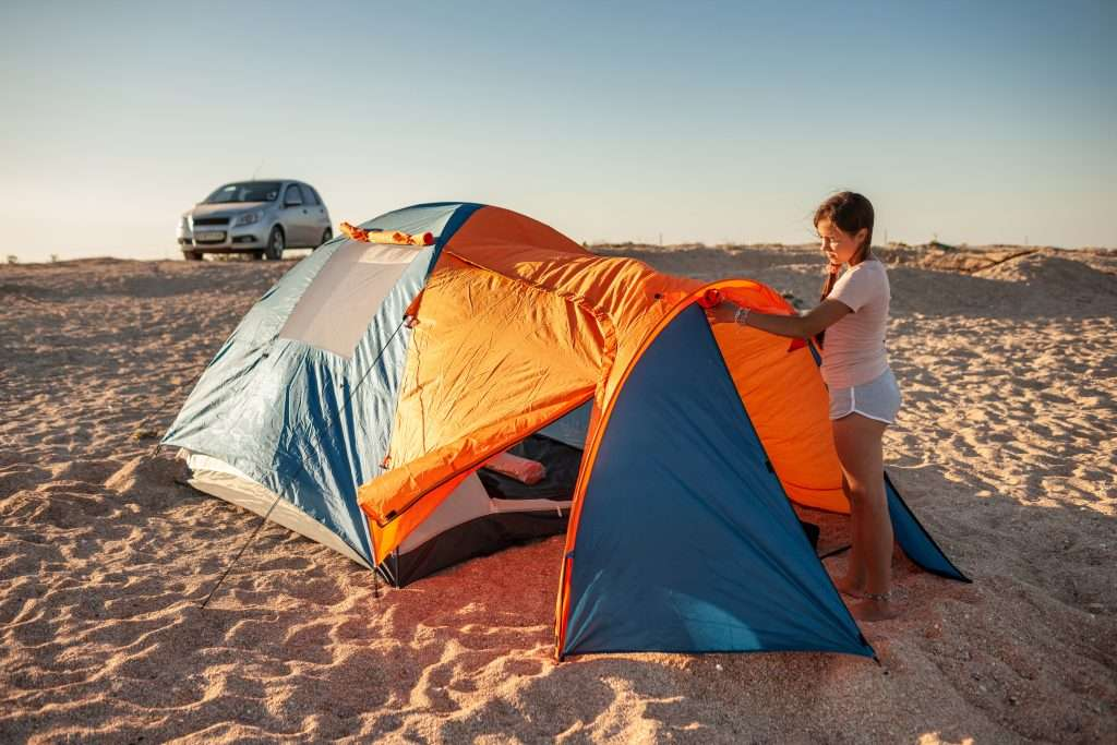 Girl setting up tent on beach to beach camp.
