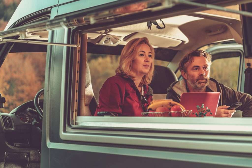 Couple watching TV from inside their RV.