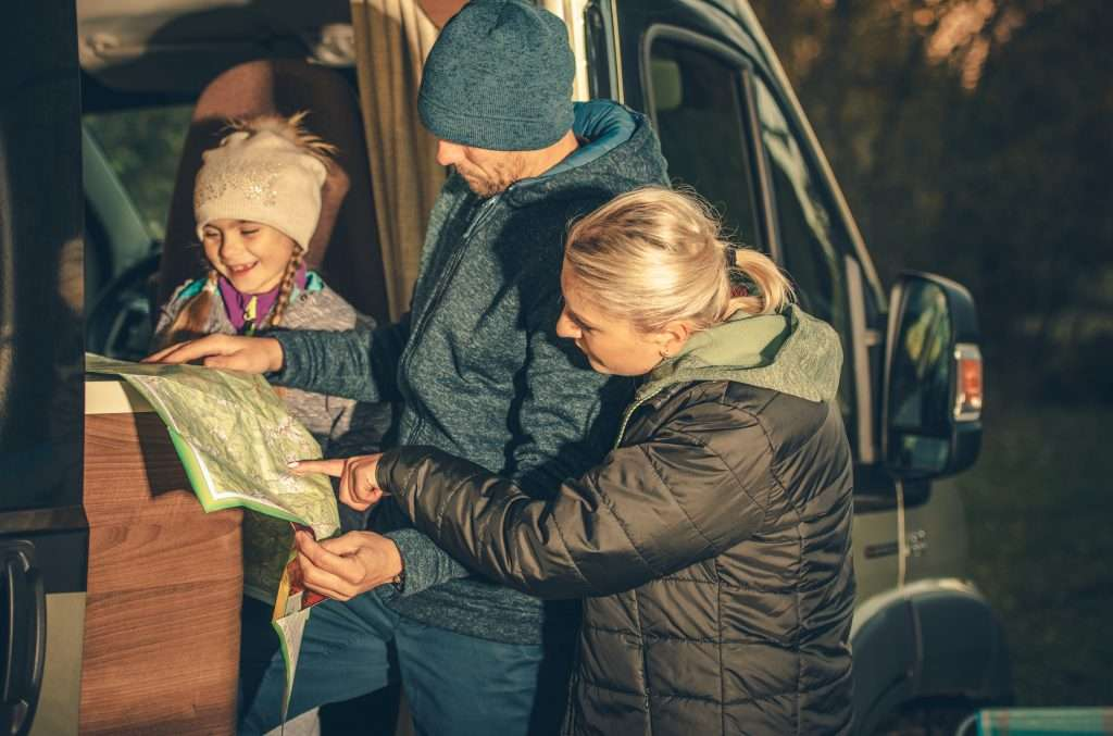 Family bundled in jackets RVing in winter.