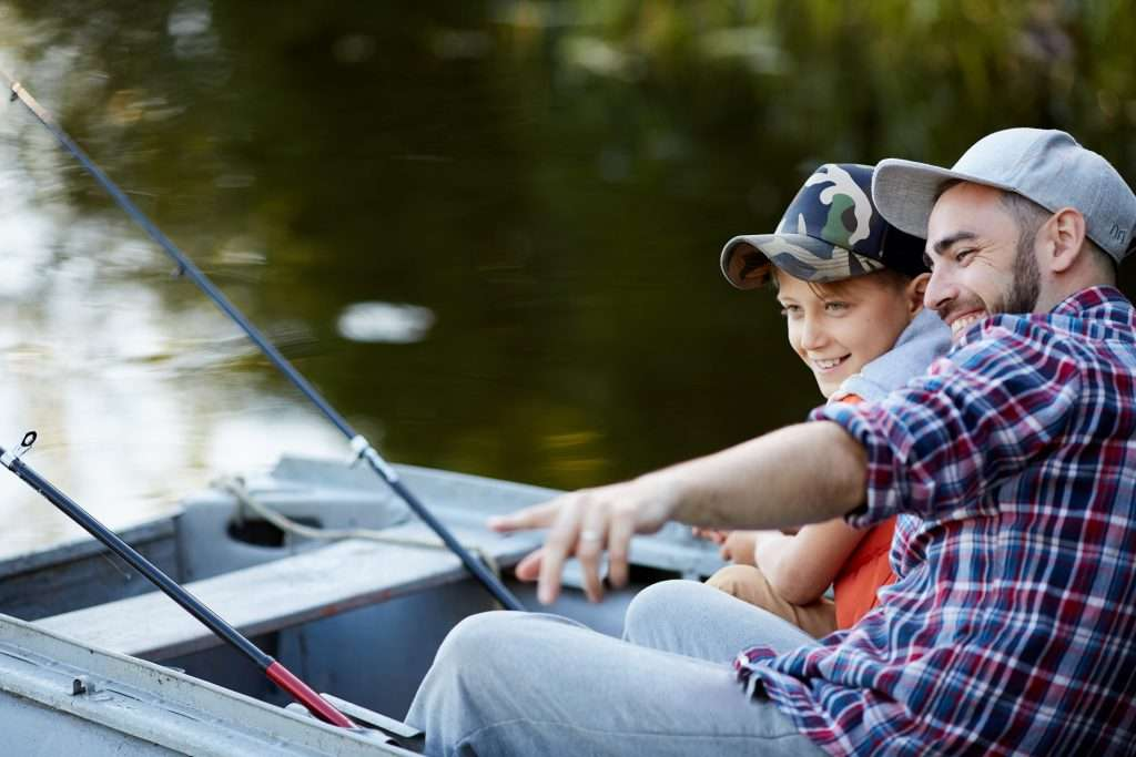 Father and son fishing in a boat.