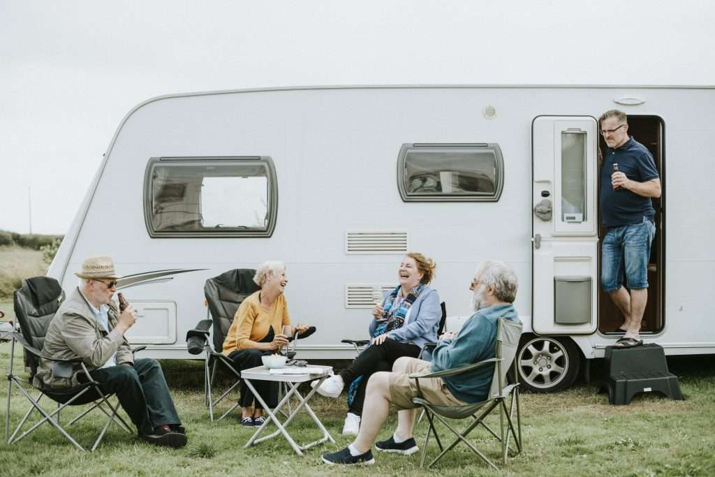 Group of older friends sitting and laughing in front of RV.