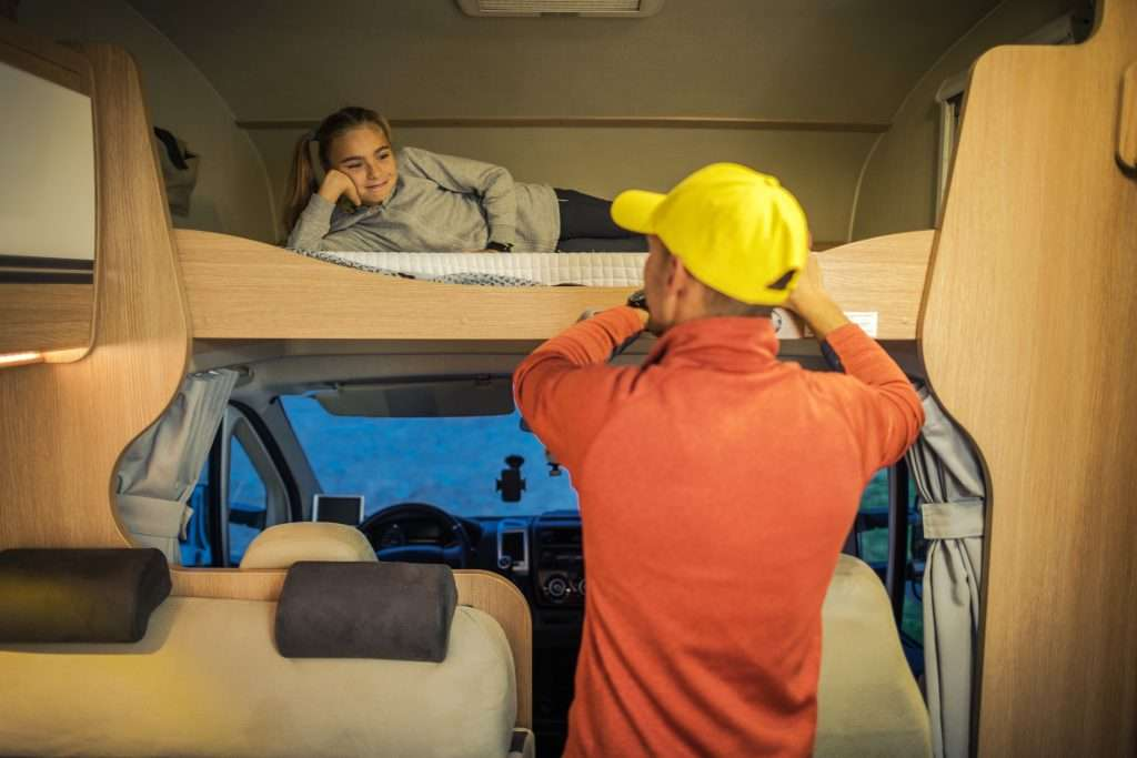 Man with his daughter inside bunk house travel trailer.