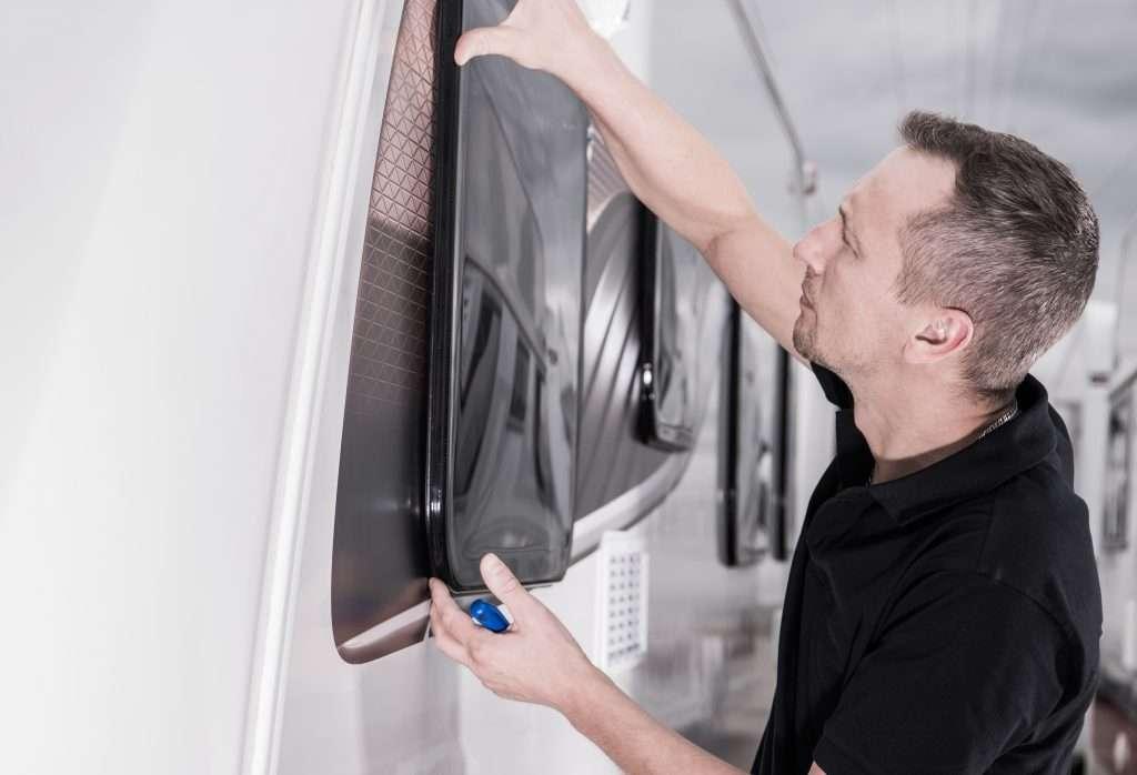 Man installing double pane windows on RV.