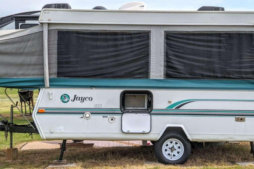 Popup camper with window air conditioner installed in storage