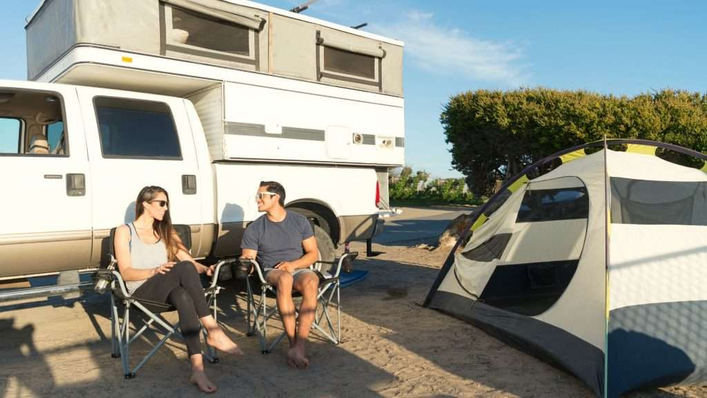 Couple sitting in front of a pop-up truck camper