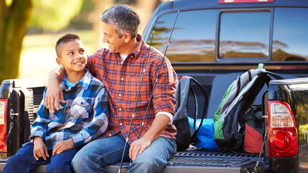 Father and son sitting on truck tailgate