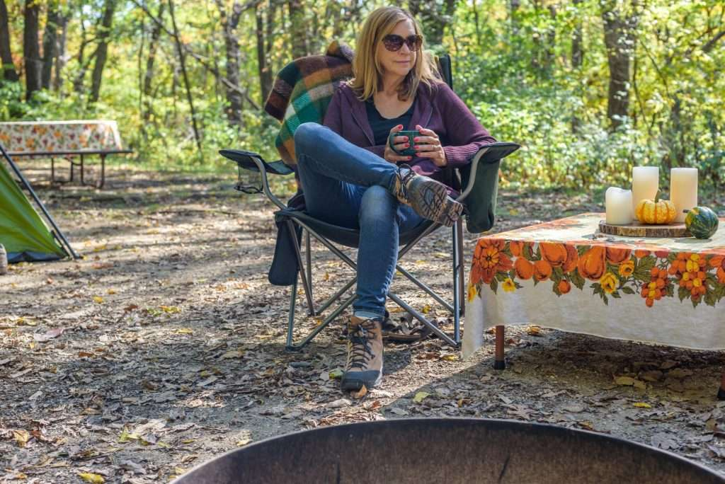 Woman sitting in chair at a campsite in a State Park.