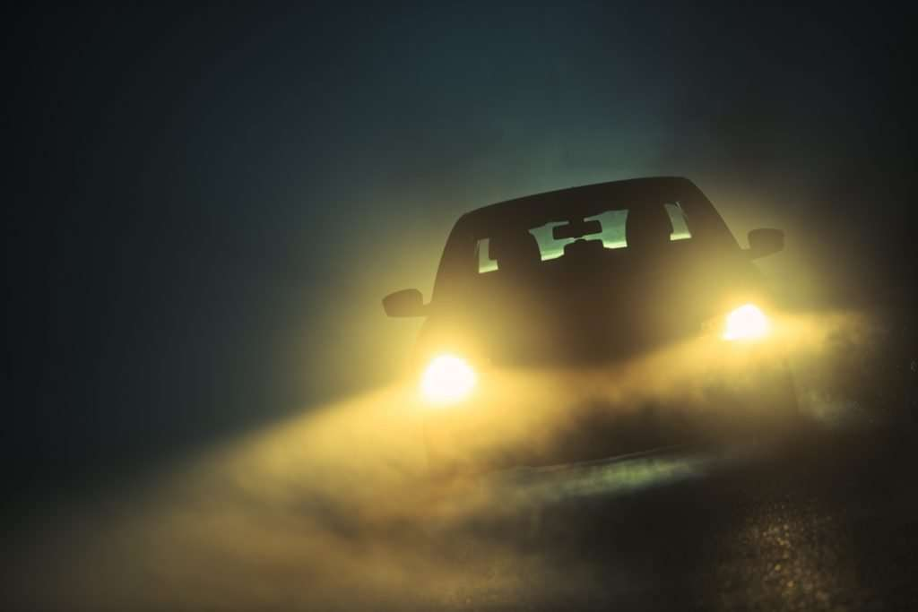Car Driving in Dense Fog with yellow lights.