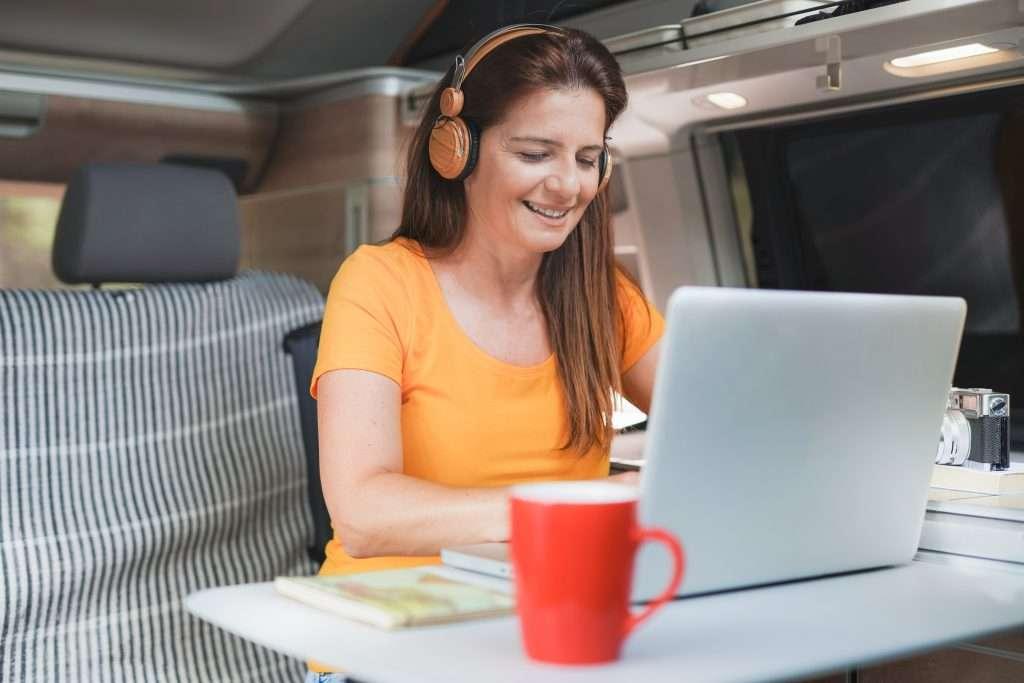 Woman working from inside her minivan camper.