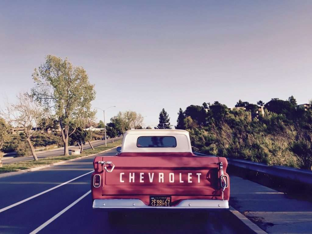 Vintage Chevrolet driving down highway.