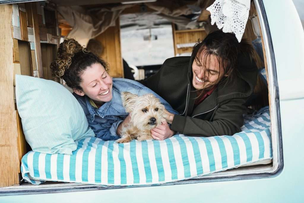 Happy couple and dog laying in their camper van