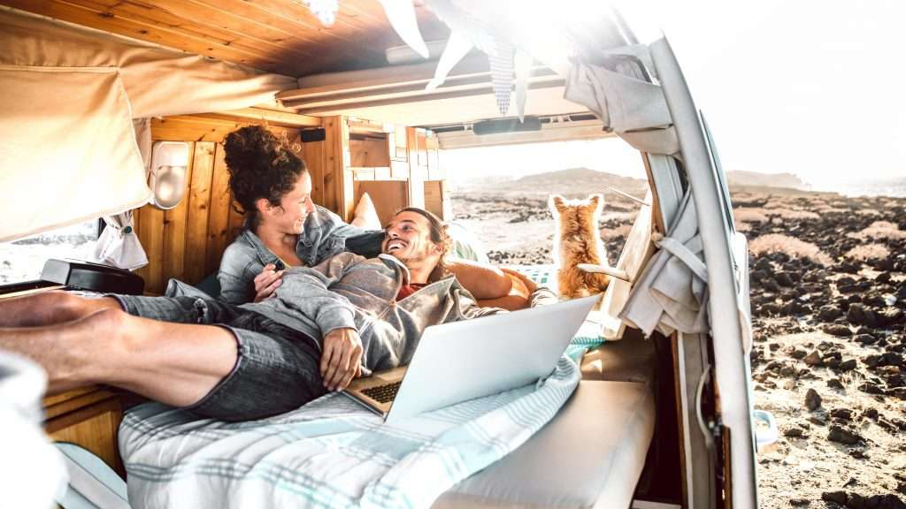 Happy couple and dog laying in their minivan camper.