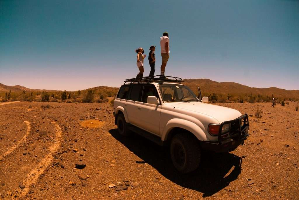 Three friends on top of their vehicle while overlanding.