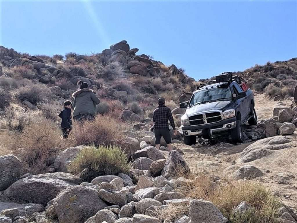 Group of friends driving truck over rocks while overlanding.
