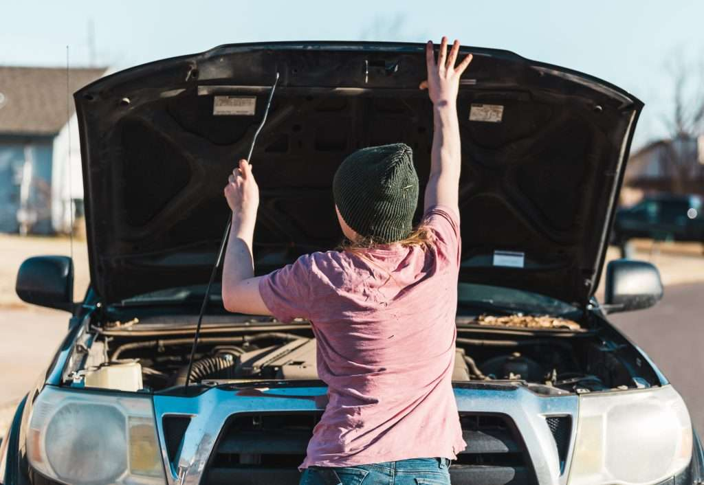 Woman looking at engine of her truck.