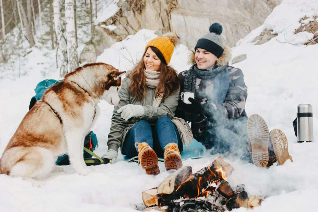 Couple sitting by camp fire in the snow with their husky.