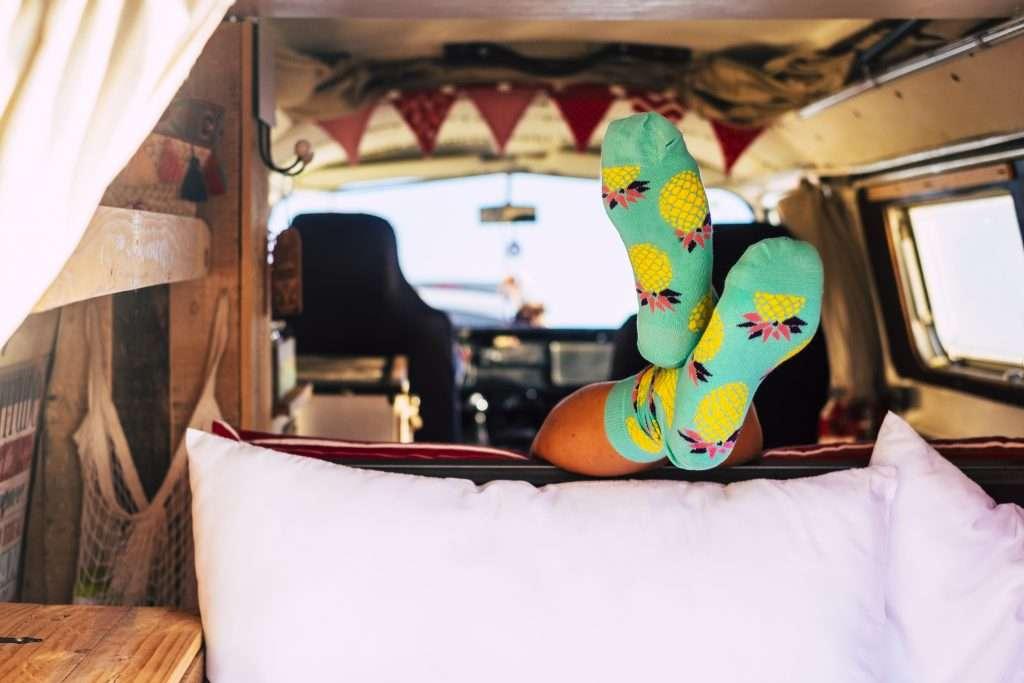 Person sleeping in minivan camper with feet up.