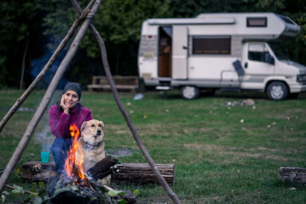 Woman and dog sitting in front of campfire and RV.