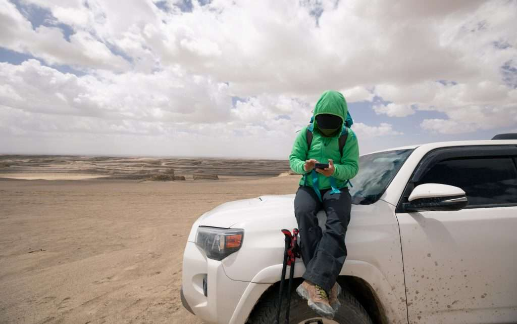 Woman researching on her phone sitting on her car while overlanding.