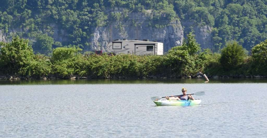 kayaker on lake with RV on road in background
