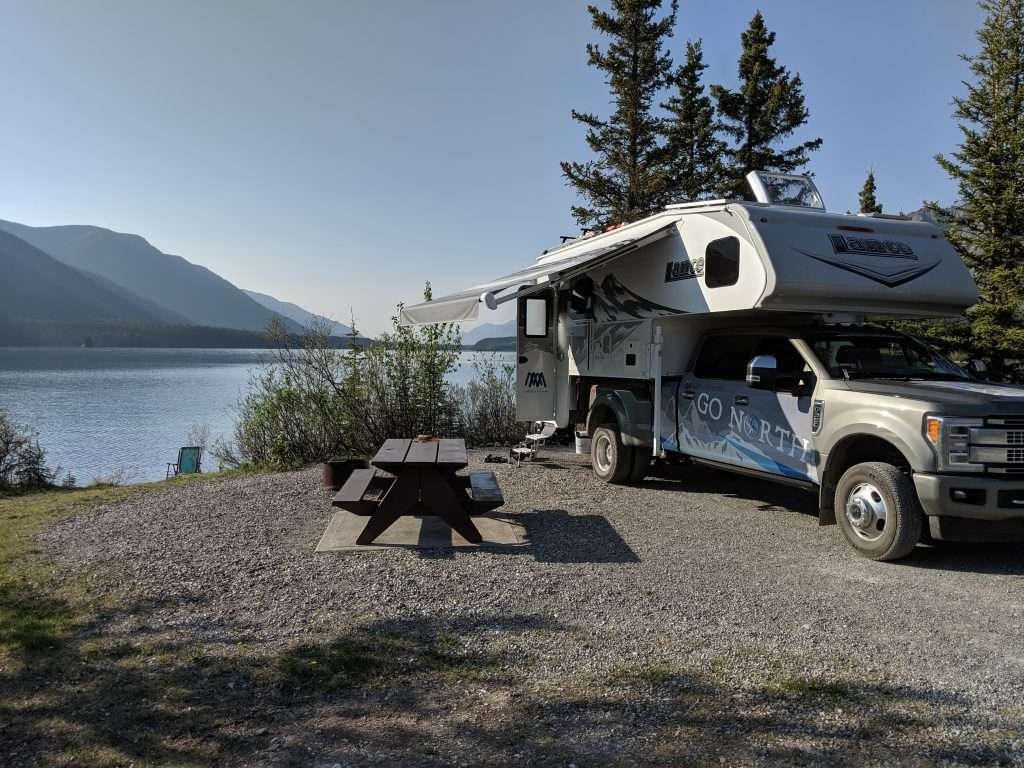 Go North truck camper parked by scenic lake with awning open.