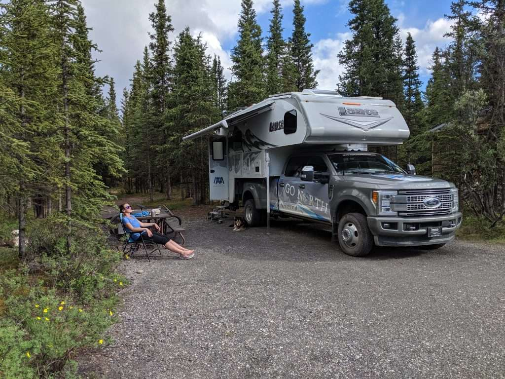 Caitlin Morton relaxing next to Go North truck camper with awning out.