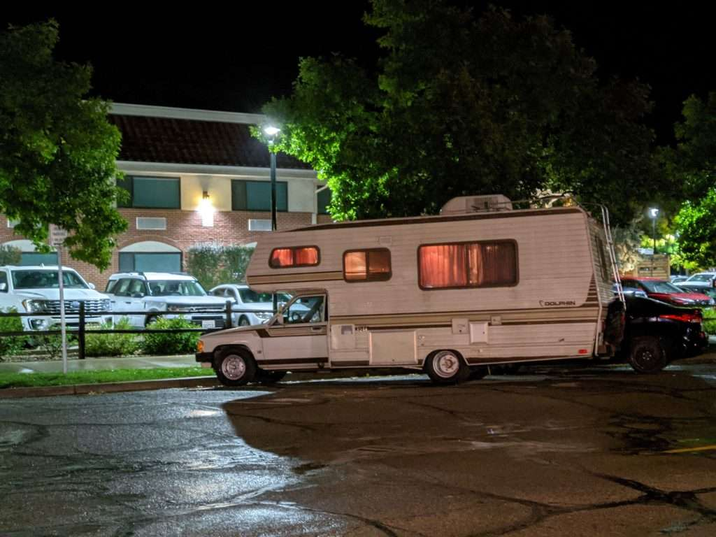 class c motorhome parked in street with  lights on inside