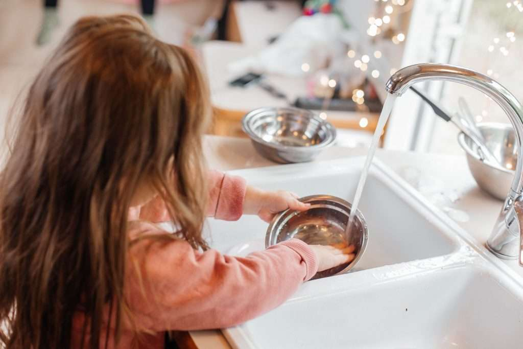 Little girl washing dishes in RV.