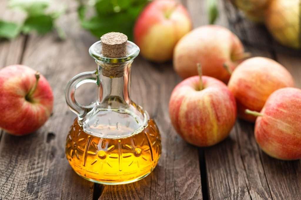 Product shot of apple cider vinegar and apples.