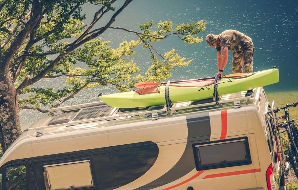 Man Installing Kayak on the RV Camper Van.